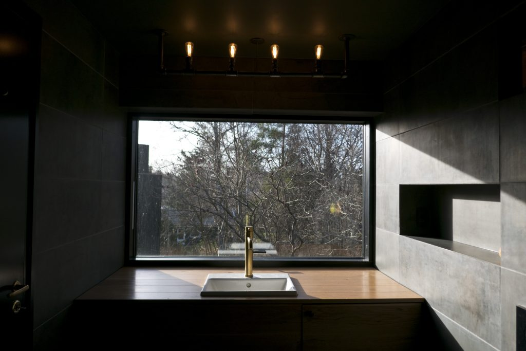 hus på skrånende grund muliggører et badeværelsesvindue uden indkig