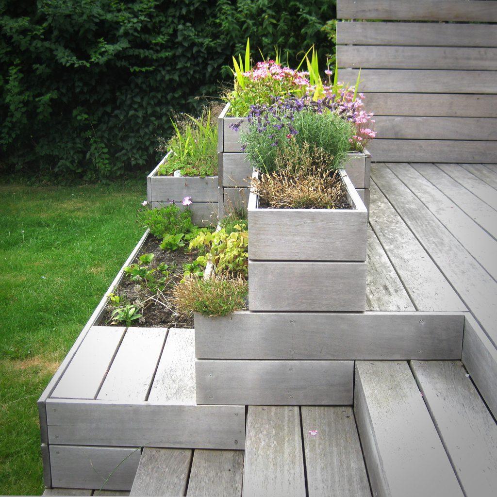 blomsterkasser skærmer mellem græsplæne og hævet terrasse
